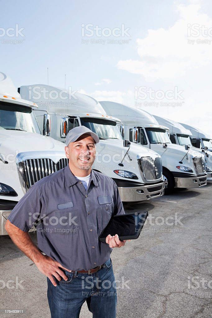 Truck driver in front of big rigs with digital tablet stock photo