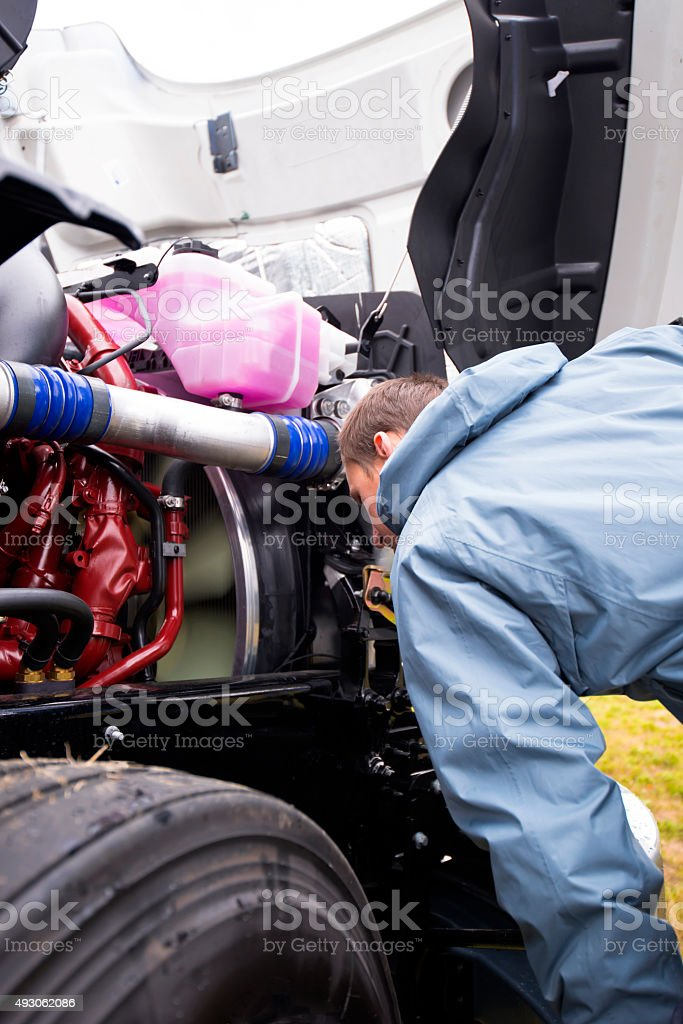 Truck driver inspects the running engine of large semi truck stock photo