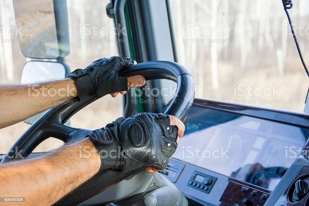 Truck driver keeps driving wheel with both hands stock photo