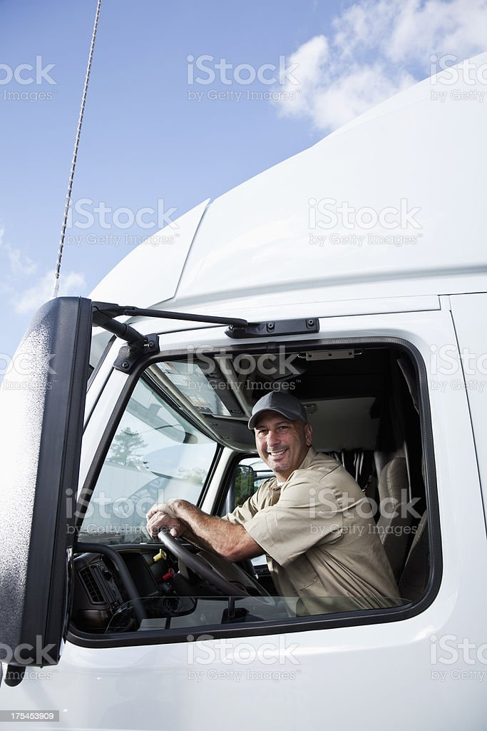 Truck driver sitting in cab of semi-truck royalty-free stock photo
