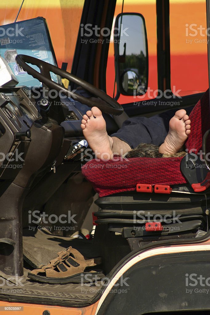 Truck driver sleeping in front seat with bare feet stock photo