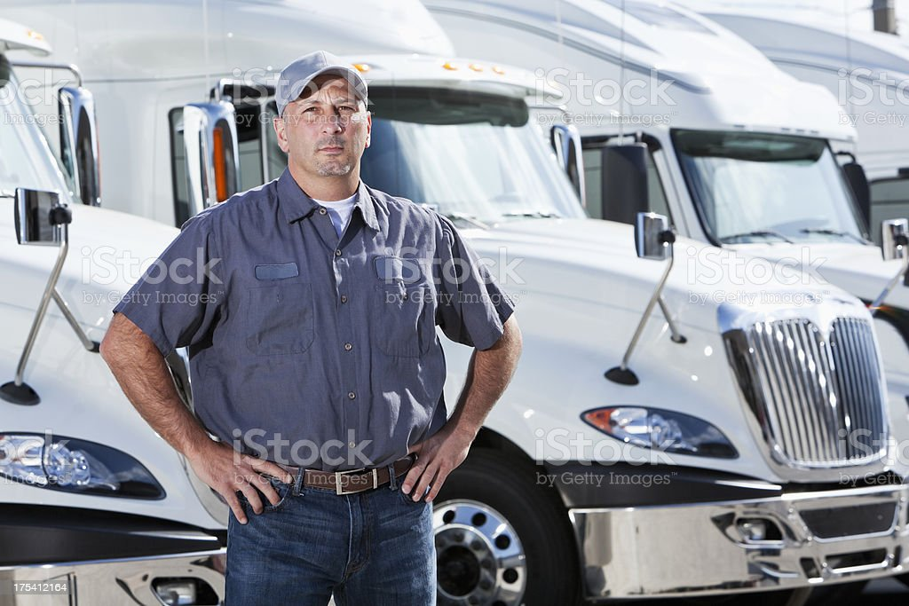 Truck driver standing in front of big rigs stock photo