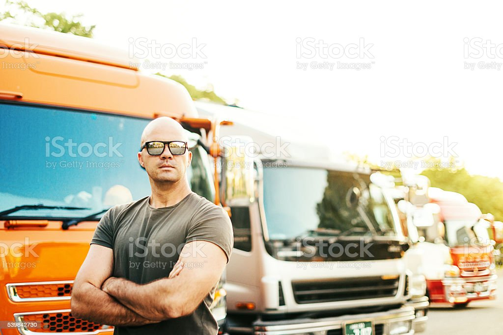 Truck driver standing in front of truck fleet stock photo