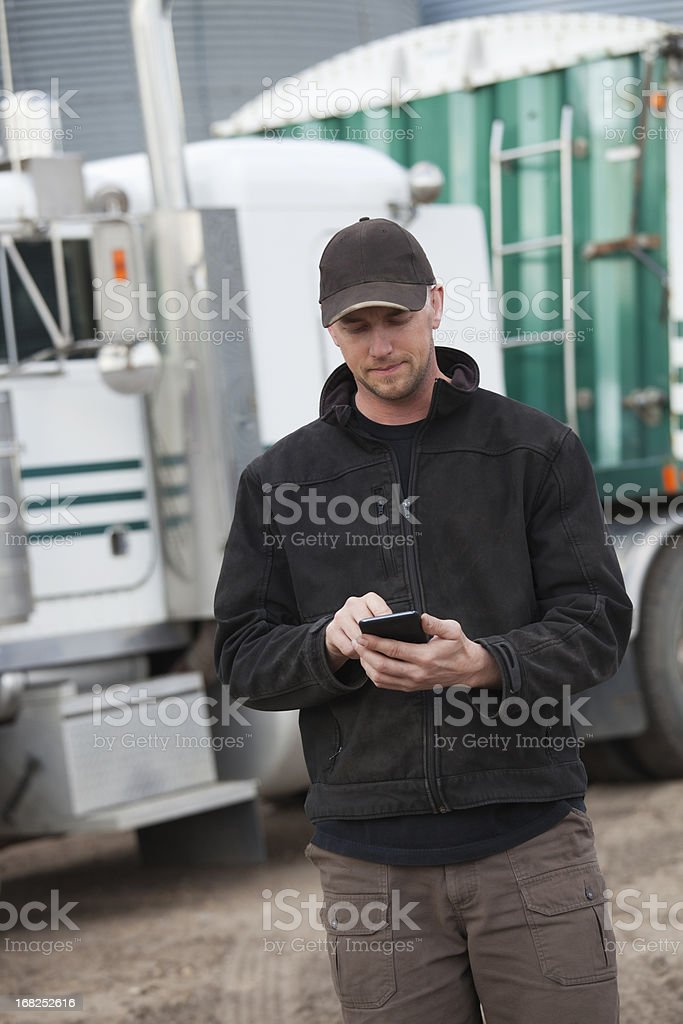 Truck driver using smartphone with semi in background royalty-free stock photo