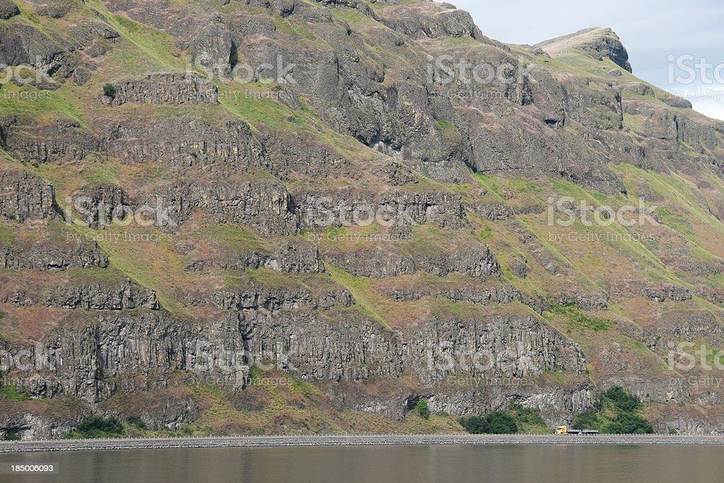 Truck driving on riverside under basalt cliff royalty-free stock photo
