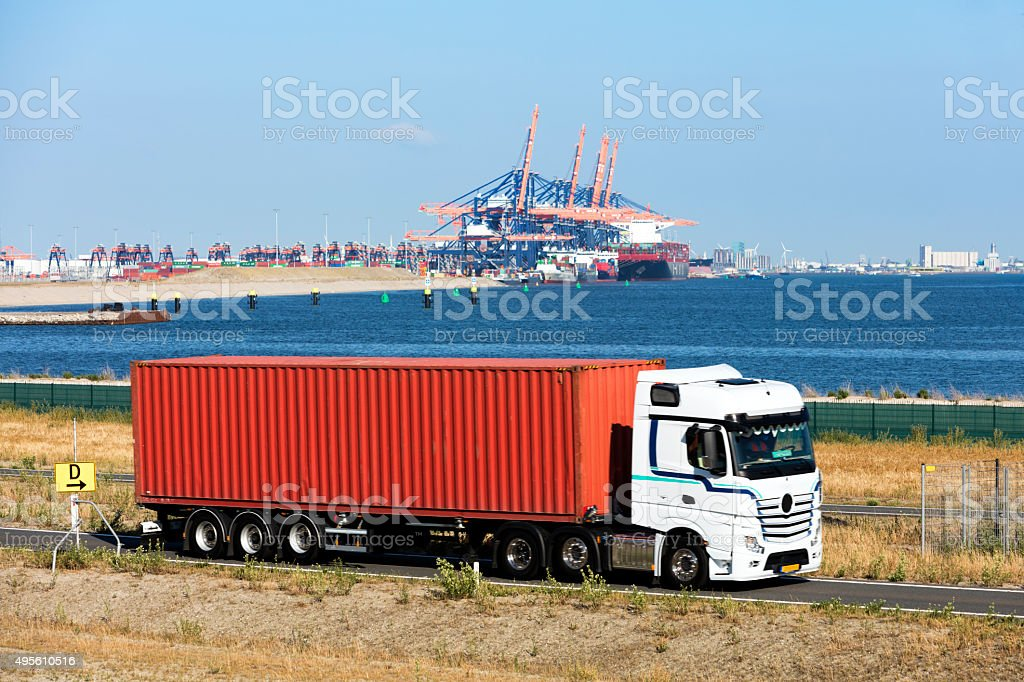 Truck Driving on Road in Front of Harbor stock photo