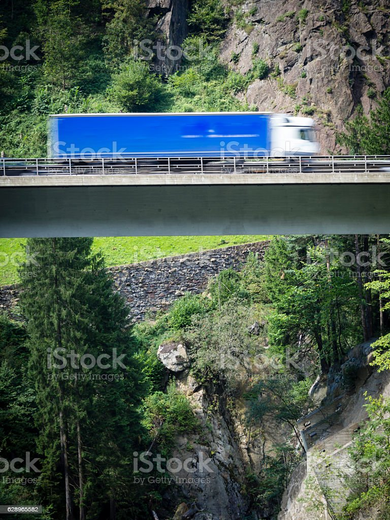 Truck driving on suspended highway / alpine mountain viaduct stock photo