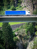Truck driving on suspended highway / alpine mountain viaduct