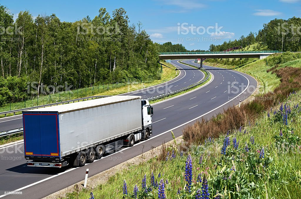 Truck driving on the highway with a double bend stock photo