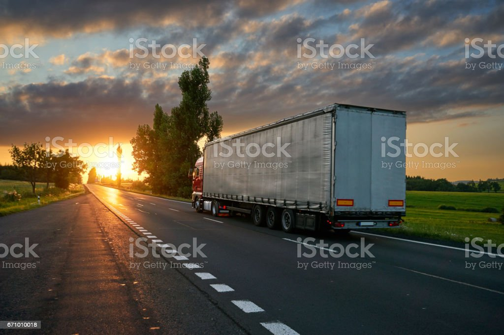 Truck driving toward the setting sun on the road stock photo