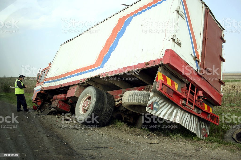 Truck lying in a ditch with policeman investigating stock photo