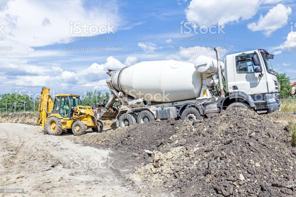 Truck mixer in process of pouring concrete into bulldozer scoop. stock photo
