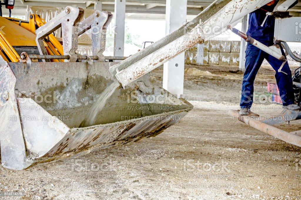 Truck mixer in process of pouring concrete into bulldozer scoop stock photo