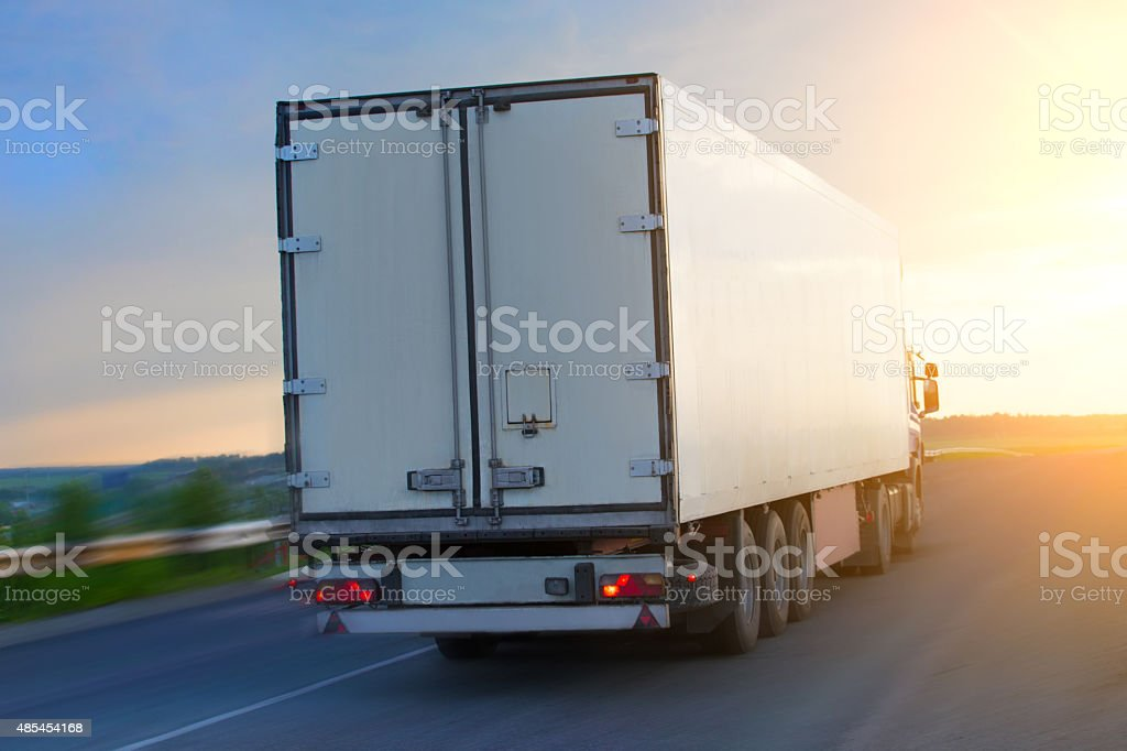 truck moves on highway at sunrise stock photo