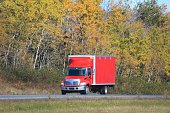 Truck on an interstate highway, trees in background.