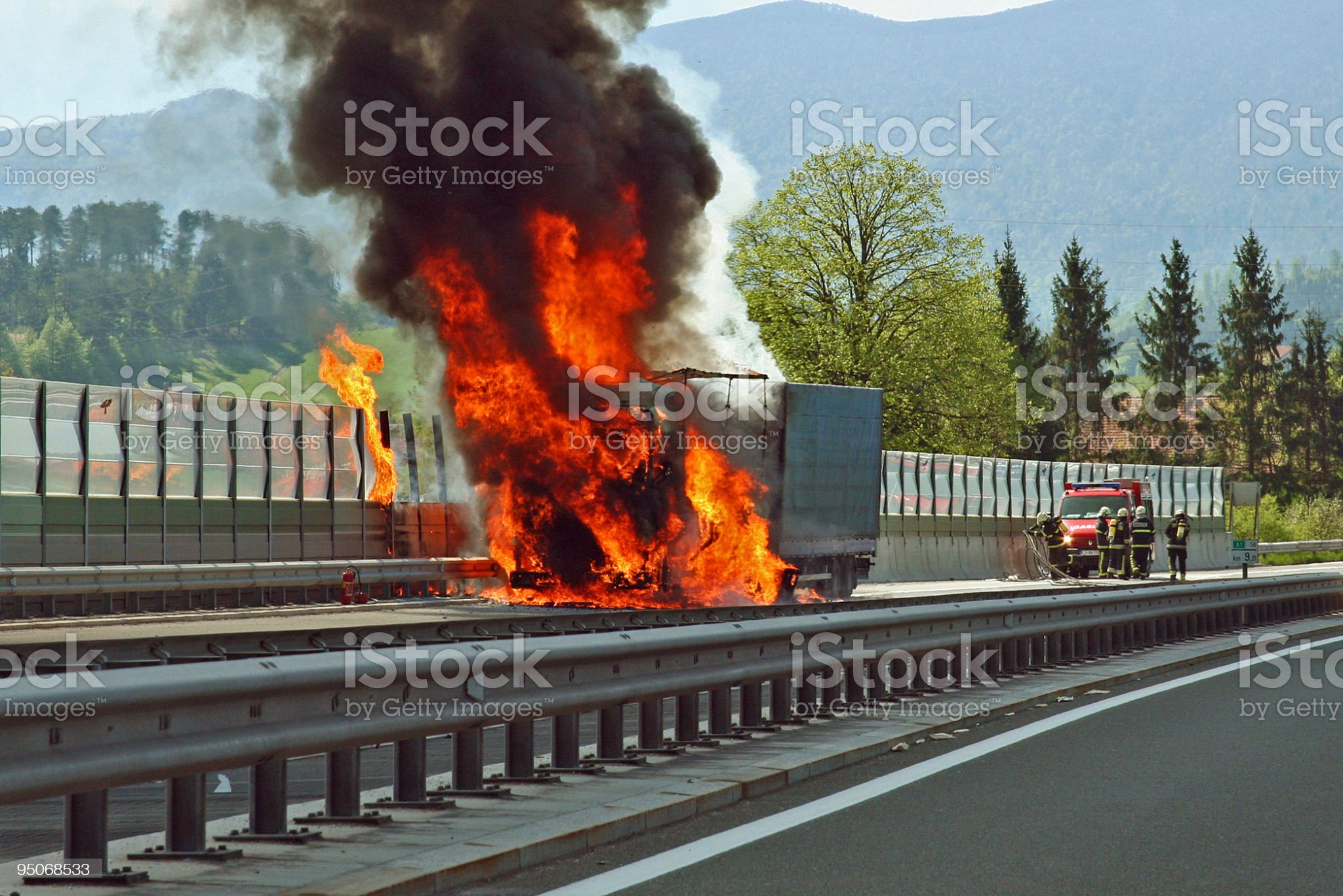 Truck on fire on a highway with firefighters approaching royalty-free stock photo
