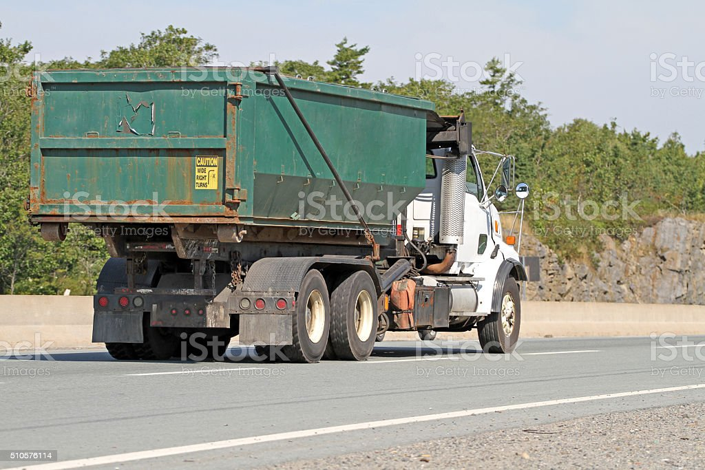 Truck On Highway Transporting An Industrial Waste Bin stock photo