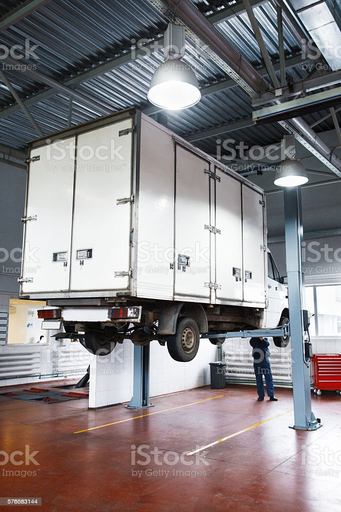 Truck service in garage, lifted lorry diagnostics stock photo