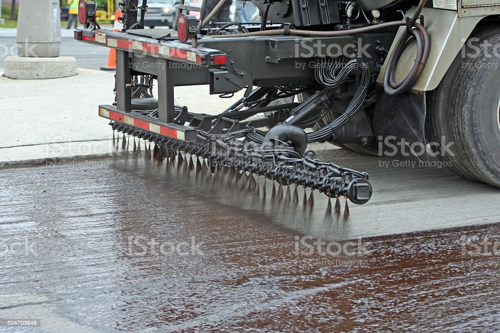 Truck Spraying Hot Tar On Road Prior To Asphalt Paving stock photo
