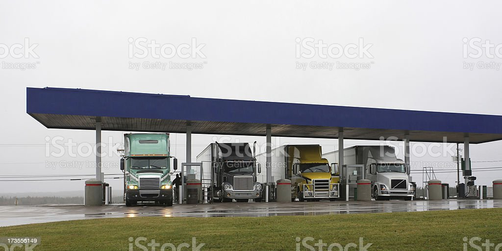 Semi tractor trailer trucks fill up with diesel fuel at a busy truck...