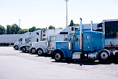 Truck stop with row of big rigs semi trucks