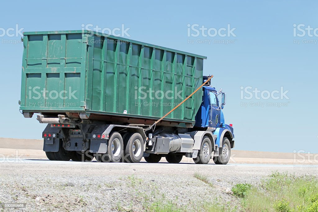 Truck Transporting Large Industrial Bin On Highway, Waste Management stock photo