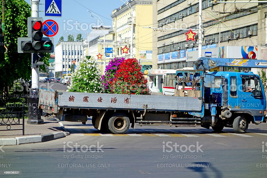 Truck transports flower beds stock photo