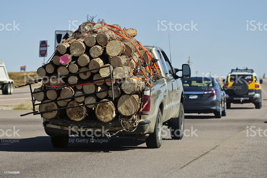 Truck Travelling on Roadway Heavily Overloaded by Wood stock photo