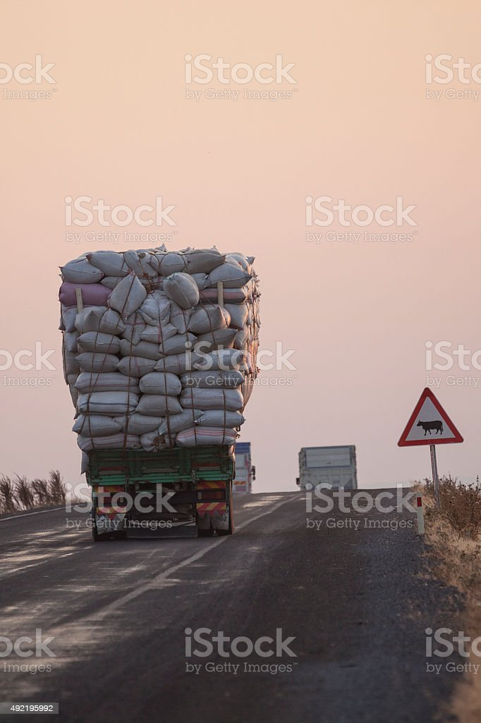 Truck under heavy weight on the road during sunset. stock photo