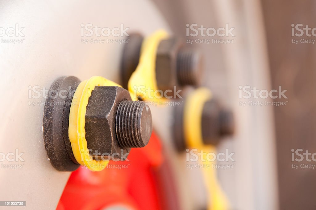 Truck wheel studs, rim with yellow loose nut indicators stock photo