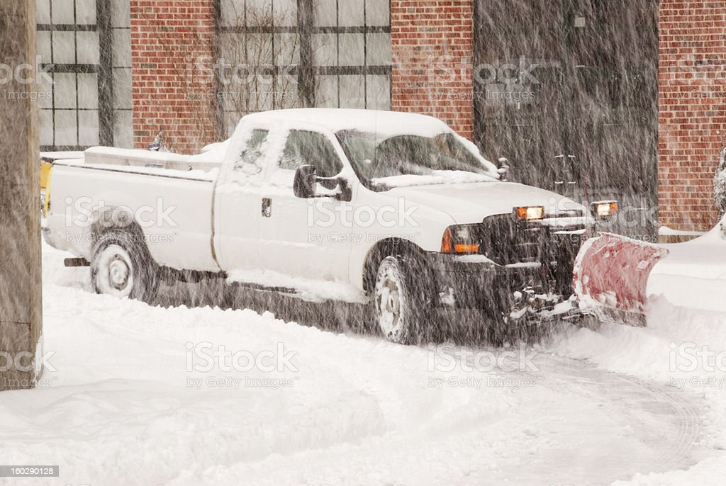 truck with a snowplow clearing a road during a blizzard stock photo