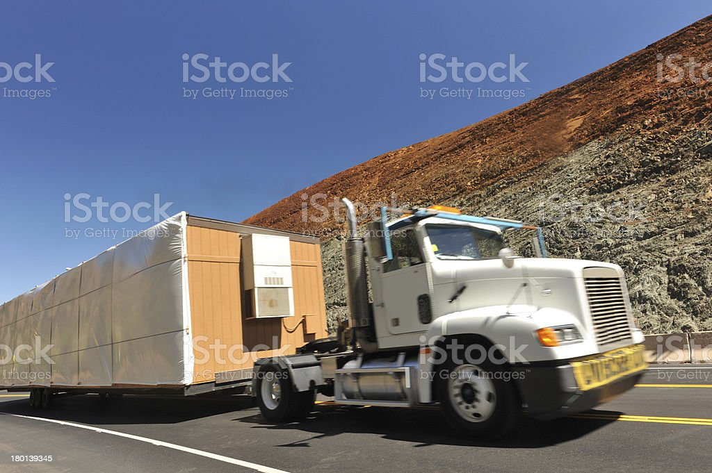 Truck with a wide load moving up hill stock photo