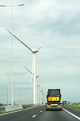 Truck without trailer on highway  with windturbines