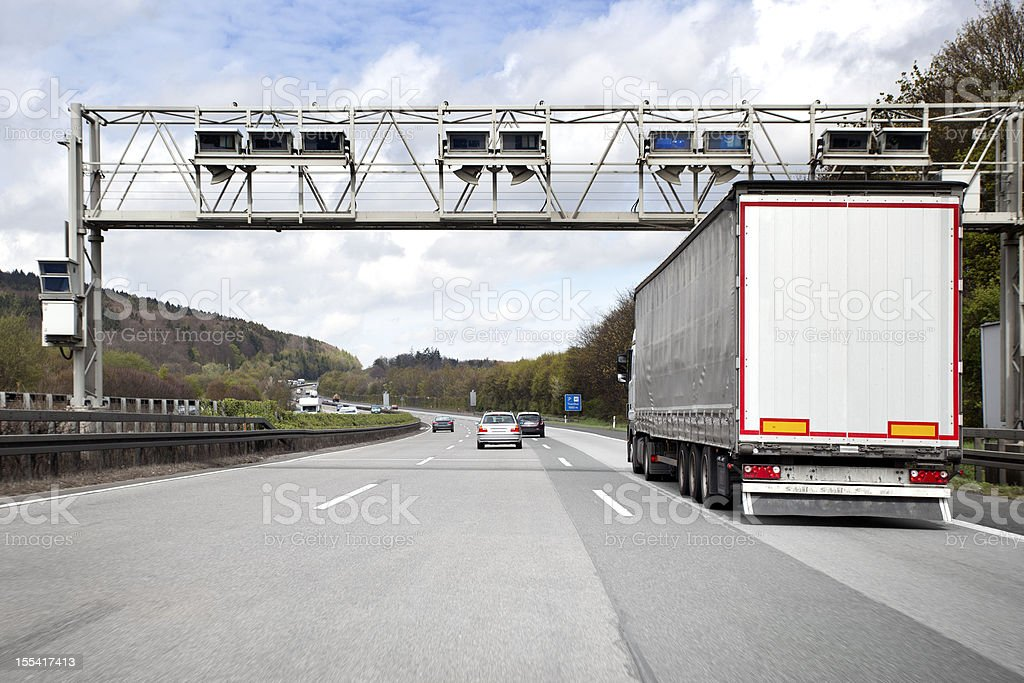 Trucks and cars on german highway, toll system gantry stock photo