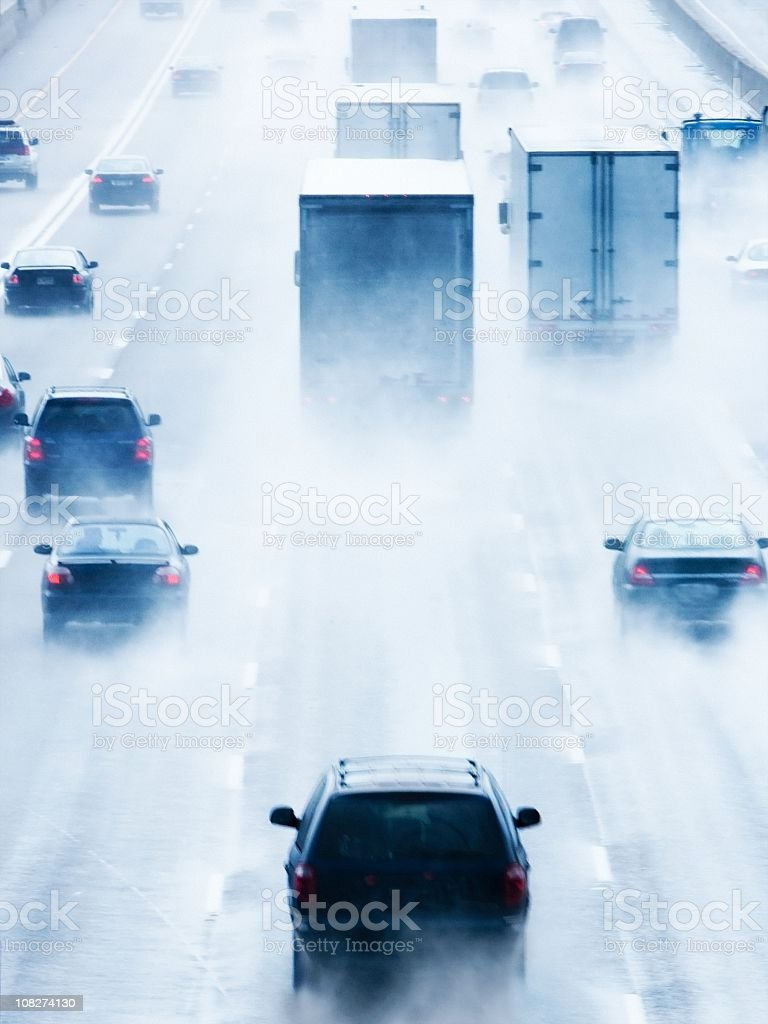 Trucks and Cars Traveling in Rain stock photo