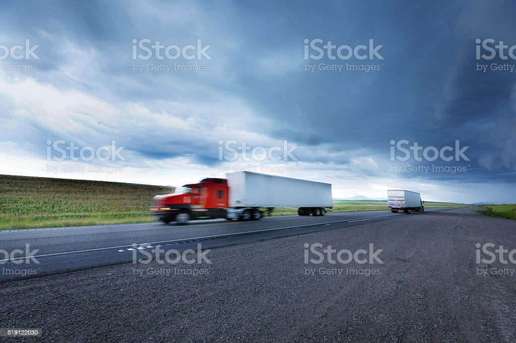 Trucks Driving Through Storm Over the Highway stock photo