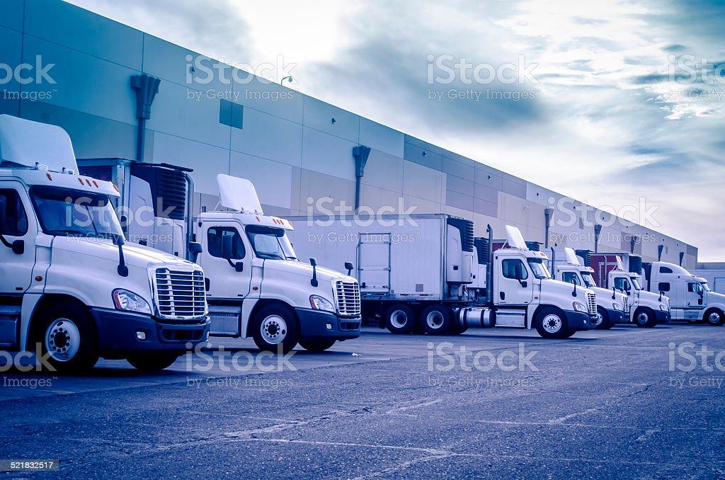 Trucks loading unloading at warehouse stock photo