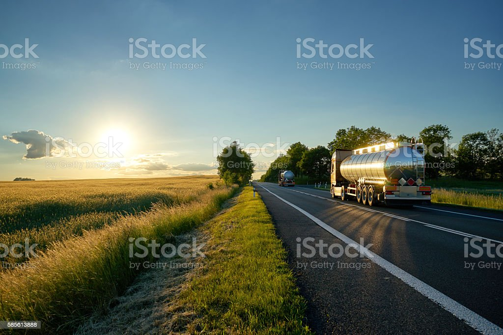 Trucks with chrome tank driving on road at sunset. stock photo