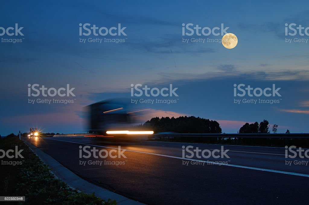Trucks with glowing lights arriving on the motorway. stock photo