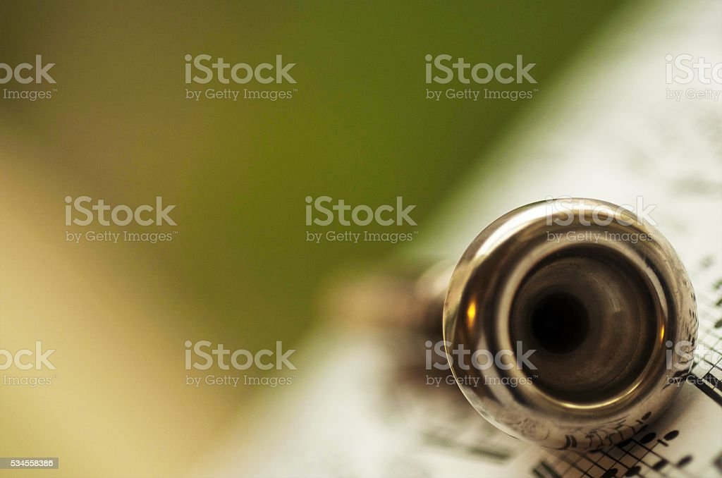 trumpet mouthpiece posed on a book of music sheets stock photo