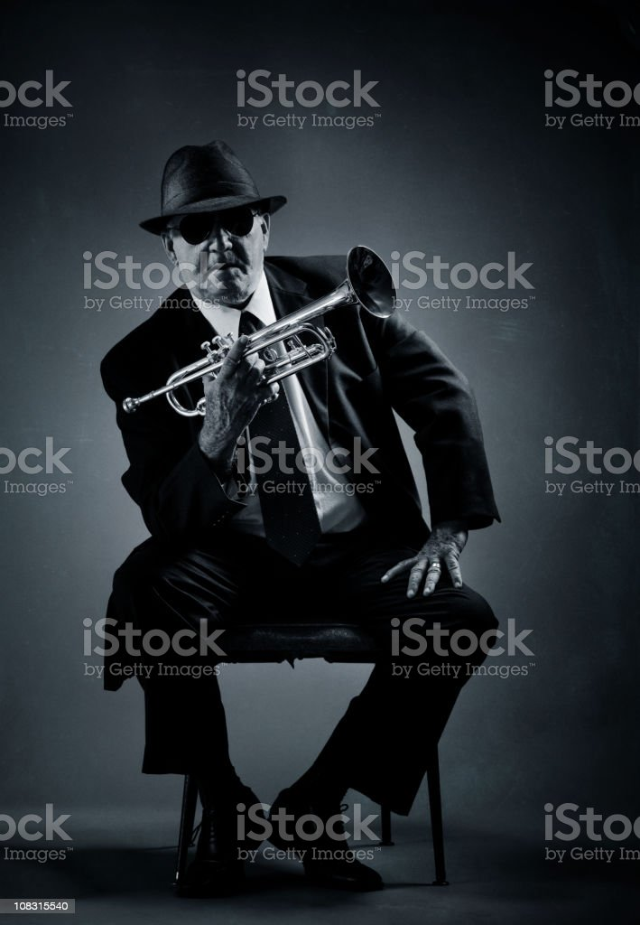 trumpet player resting on a chair royalty-free stock photo