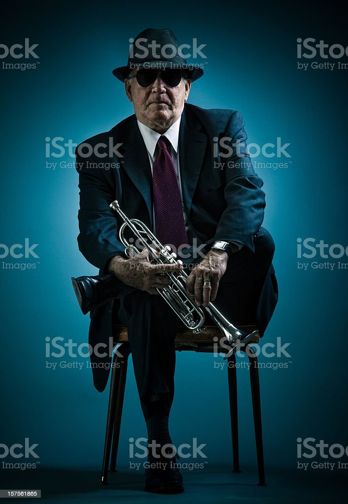 trumpet player resting on a chair stock photo