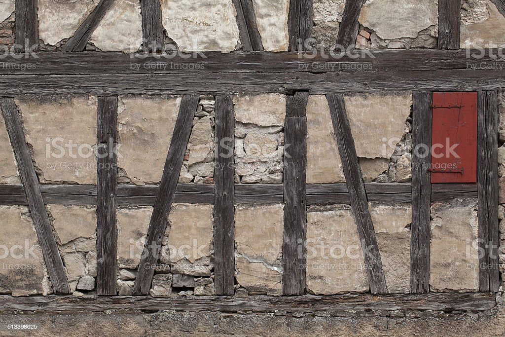 Truss of a ramshackle barn with a small red shutter royalty-free stock photo