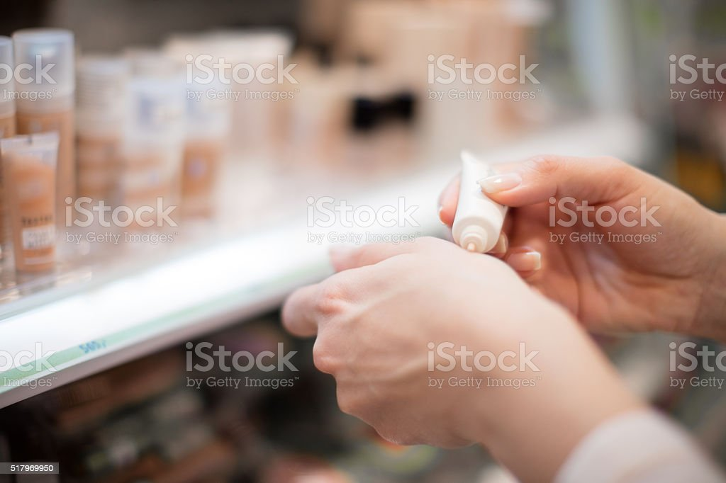 Trying concealer in cosmetics store stock photo