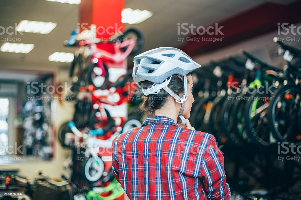 Trying new sports helmet in the bike shop stock photo