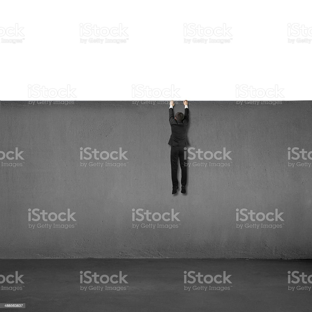 Trying to climb over wall stock photo