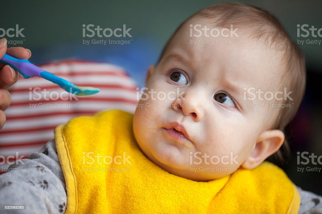 Trying to feed a baby boy stock photo
