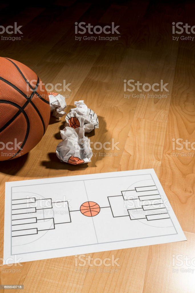 Trying to fill out college basketball tournament bracket on paper stock photo
