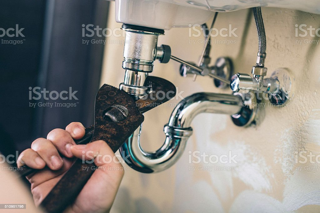 Trying to fix the drain stock photo