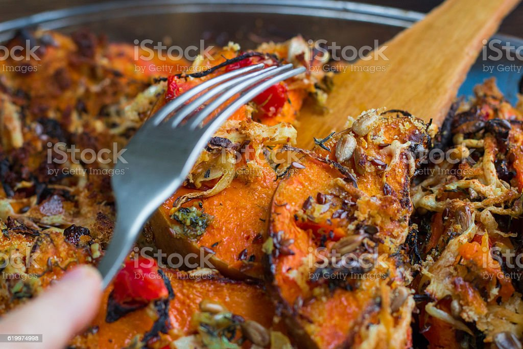 Trying vegetarian baked orange pumkin, vegetables, herbs, cheese with folk stock photo
